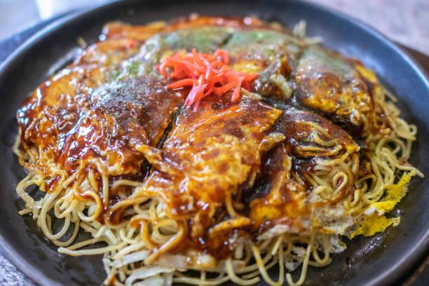 hiroshima-style okonomiyaki in hiroshima prefecture, japan. okonomiyaki is a japanese-style pancake made from egg, flour and water with lots of toppings. - hiroshima zdjęcia i obrazy z banku zdjęć