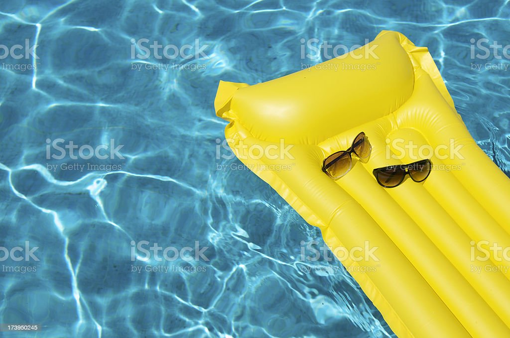 His and Hers Sunglasses on Pool Raft royalty-free stock photo
