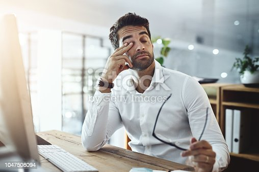 Shot of a young businessman looking stressed out and tired while working in an office