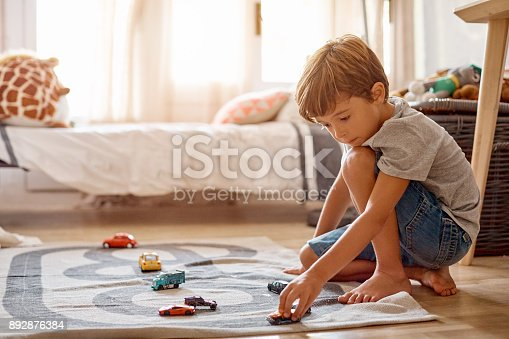 Shot of a little boy playing with his toys at home
