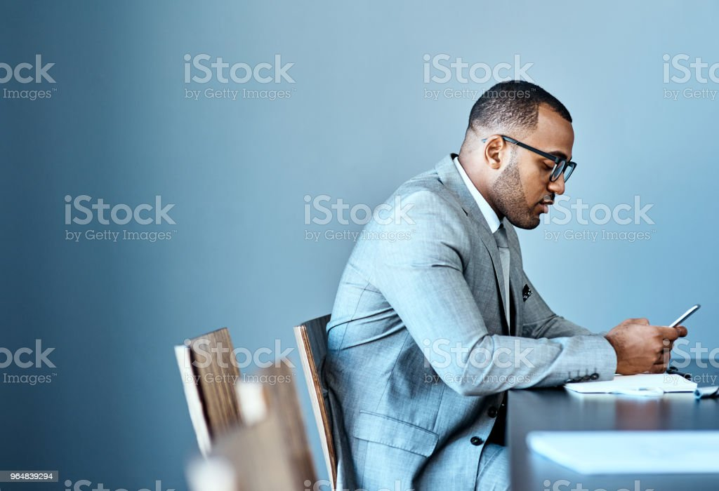 His cellphone keeps him updated with everything in business royalty-free stock photo