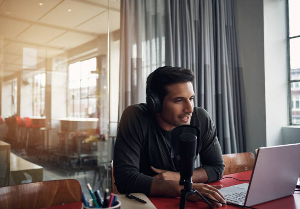 His company is joining the podcast craze Shot of a young man recording a podcast on a laptop in a modern office radio dj stock pictures, royalty-free photos & images