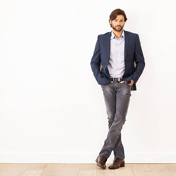 His confidence knows no bounds Portrait of a confident young businessman leaning against a white wallhttp://195.154.178.81/DATA/istock_collage/0/shoots/783044.jpg smart casual stock pictures, royalty-free photos & images