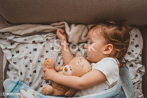 Baby sleeping on sofa. Peaceful baby lying on a bed while sleeping in a bright room with his teddy bear. Photo of Child boy sleeping with teddy bear on the bed in his bedroom, New family and baby healthy concept. Top view of Sweet Caucasian  one year old child sleeping with teddy bear during the day.