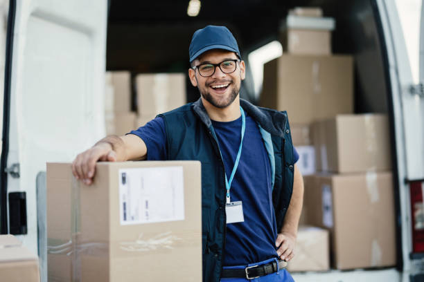 His deliveries always arrive on time! Young happy delivery man loading cardboard boxes in a van and looking at camera. delivery man stock pictures, royalty-free photos & images