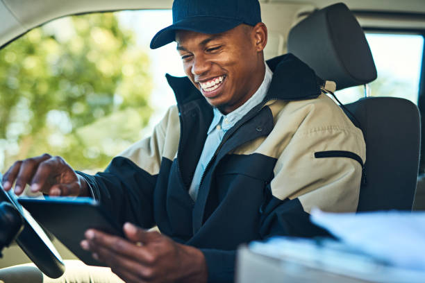 His deliveries are all digitally organized Shot of a courier using a digital tablet while sitting in a delivery van driver occupation stock pictures, royalty-free photos & images