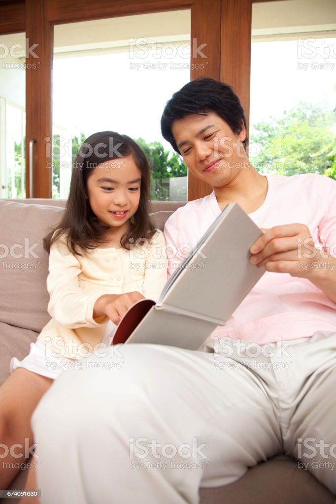 His father read the book with her daughter royalty-free stock photo