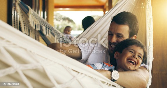 Cropped shot of a father tickling his adorable son on a hammock outside