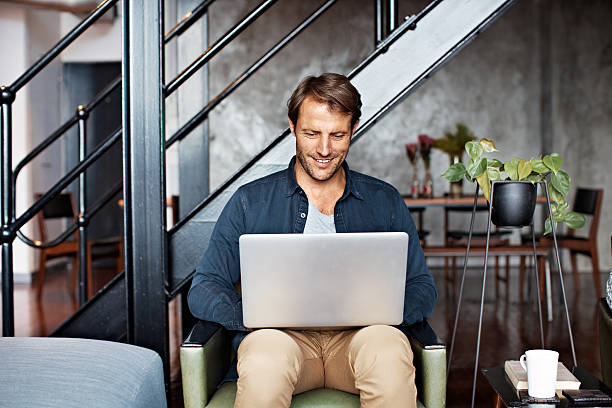 His house is totally wireless Shot of a mature man sitting on a chair in his living room using a laptop mid adult stock pictures, royalty-free photos & images