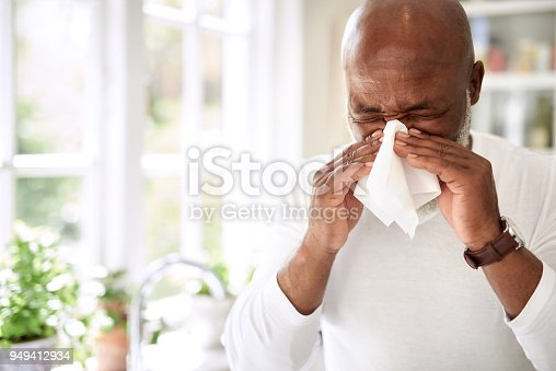 Shot of a mature man blowing his nose at home