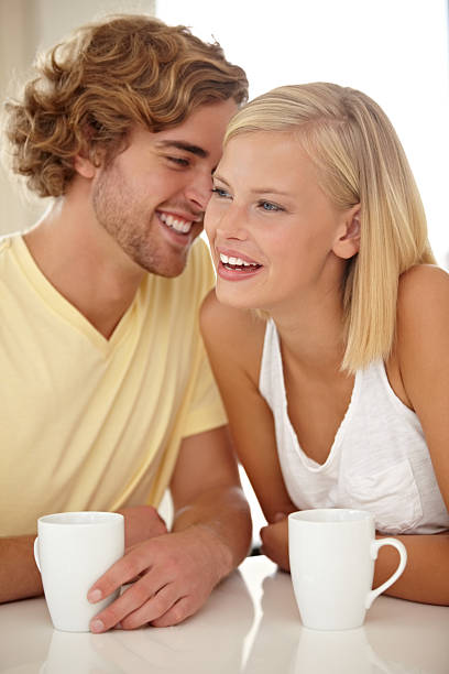 His jokes amuse her Portrait of a couple sitting together and enjoying a cup of coffee amuse stock pictures, royalty-free photos & images