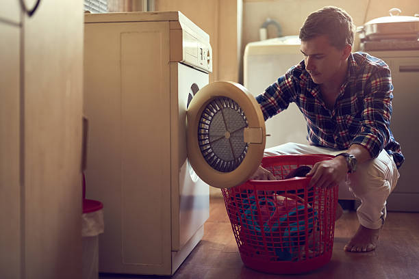 His laundry game is strong Shot of a young man doing laundry at home laundry basket stock pictures, royalty-free photos & images