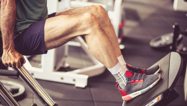 His legs go in the right direction. His legs go in the right direction. Senior man working exercise on machine for legs. Close up. exercise machine stock pictures, royalty-free photos & images