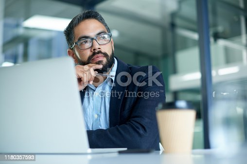 Shot of a mature businessman looking thoughtful while working on a laptop in an office