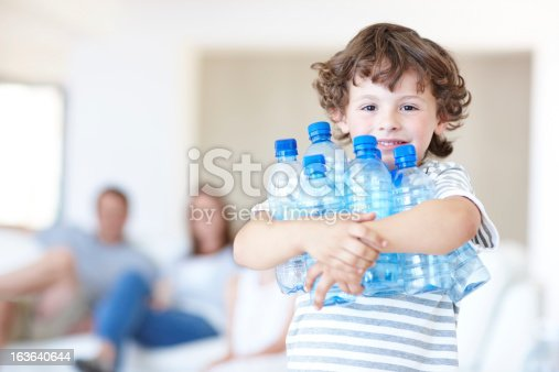 Young boy holding empty water bottles with his parents sitting in the background