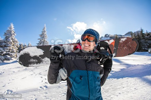 Young man carrying snowboard and enjoying white winter on the mountain