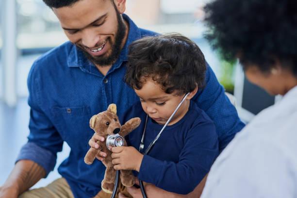 his pediatrician makes each visit as fun as possible - pediatra foto e immagini stock