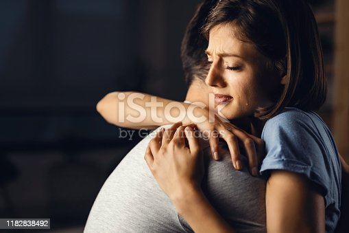 Young sad woman embracing her boyfriend while crying about something.