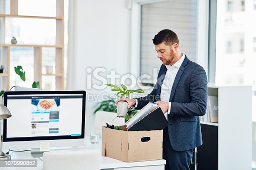 Cropped shot of a handsome young businessman packing up his desk at work after being let go