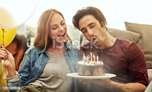 Shot of a young couple having cake while celebrating a birthday at home