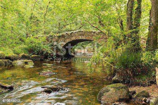 A riverside image of Hisley Bridge an old packhorse bridge over the river Bovey, shot at Dartmoor, Devon, England, UK