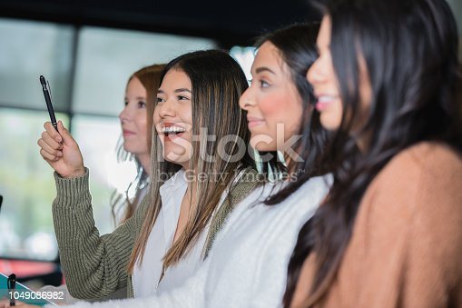 istock Hispanic adult female student asking question during lecture or seminar 1049086982