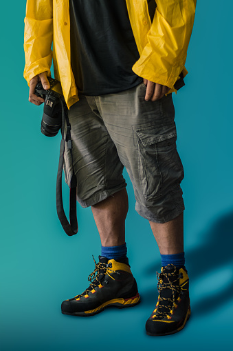 Hispanic adult male photographer wearing rain cover and hiking shoes while carrying his reflex camera against a blue background. Costa Rica, Centro America.