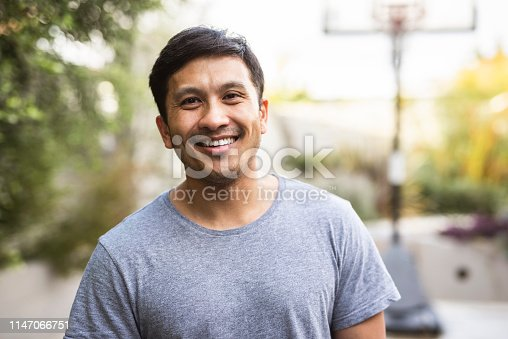 Hispanic adult standing outside and smiling