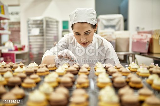 Low angle view of focused baker in mid 30s decorating fresh batch of vegan cupcakes in commercial kitchen.