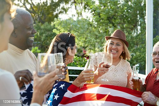Fun-loving friends in 50s, 60s, and 70s holding American flag and celebrating Independence Day holiday outdoors with beer and wine.
