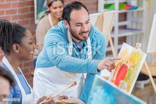 658645980 istock photo Hispanic art studio owner teaches painting lessons 659542618