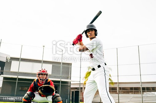 Low angle view of young Hispanic baseball catcher and player in batting stance waiting for pitcher to deliver ball.