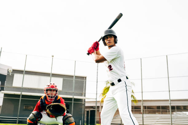 Hispanic baseball batter and catcher waiting for pitch stock photo