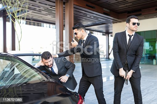 istock Hispanic Boss Getting In Car With Help Of Bodyguards 1126701383