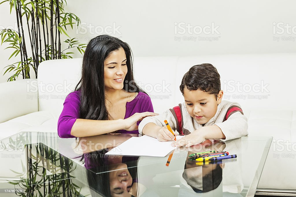 Hispanic Boy Coloring with Crayons as Mother Watches royalty-free stock photo