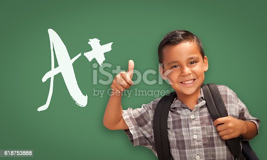 istock Hispanic Boy Gives Thumbs-up in Front of A+ on Chalkboard 618753888