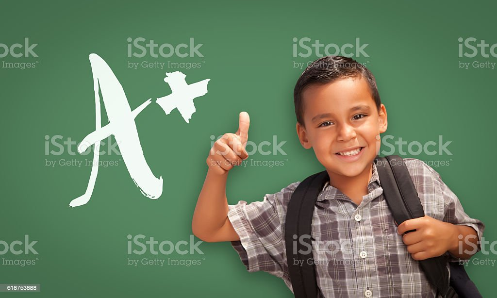 Hispanic Boy Gives Thumbs-up in Front of A+ on Chalkboard stock photo