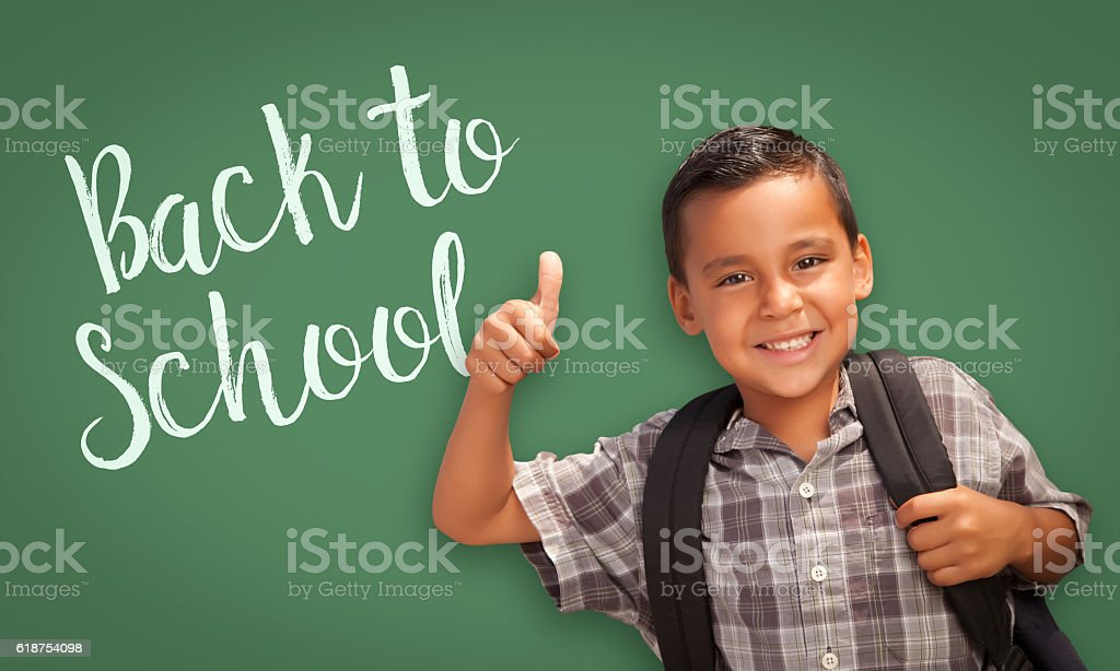 Hispanic Boy Gives Thumbs-up Near Back To School Chalk Board Cute Hispanic Boy With Thumbs Up Wearing A Backpack In Front of Chalk Board with Back To School Written On it. Agreement Stock Photo