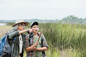 An Hispanic 12 year old boy and his grandfather, a senior man in his 80s, hiking in a park, exploring nature. They are standing and looking out toward wetlands, a grassy area by water, enjoying the view. The grandfather is pointing out something to his grandson.