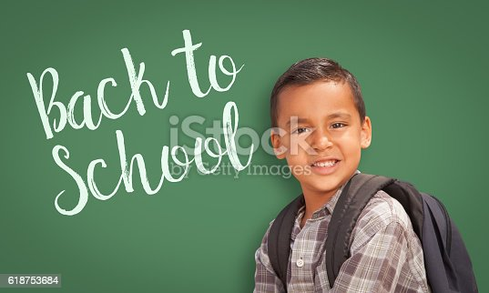 618753504 istock photo Hispanic Boy In Front of Back To School Chalk Board 618753684