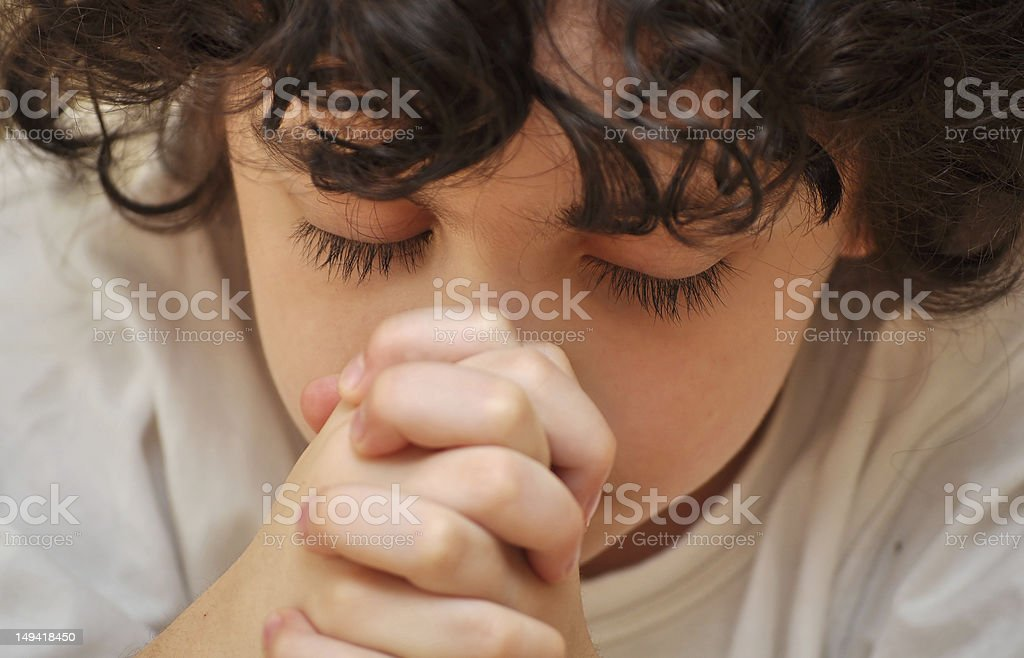 Hispanic Boy Praying with Faith and Reverence stock photo