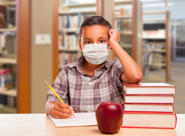 Hispanic Boy Wearing Face mask with Books, Apple, Pencil and Paper at Library stock photo