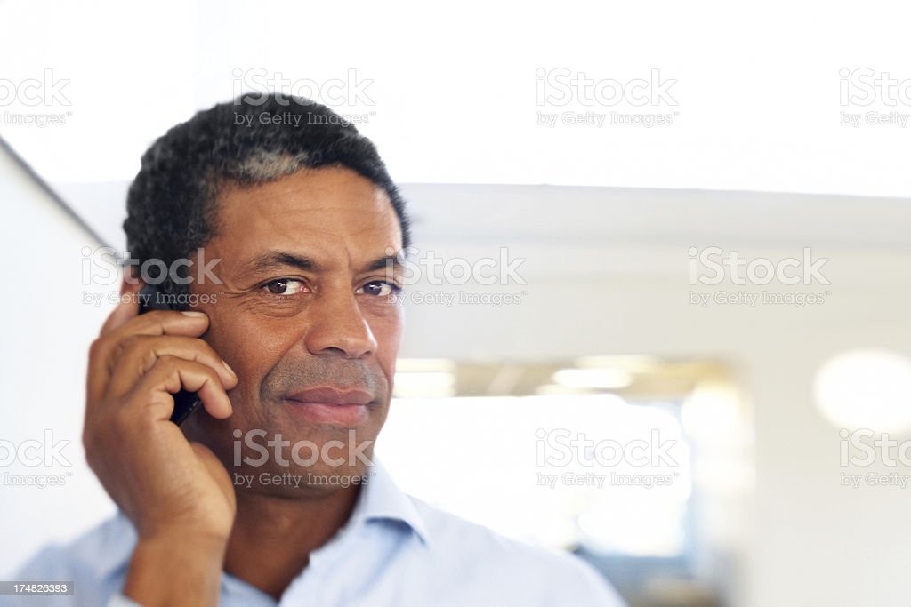 Hispanic business man using mobile phone in office royalty-free stock photo