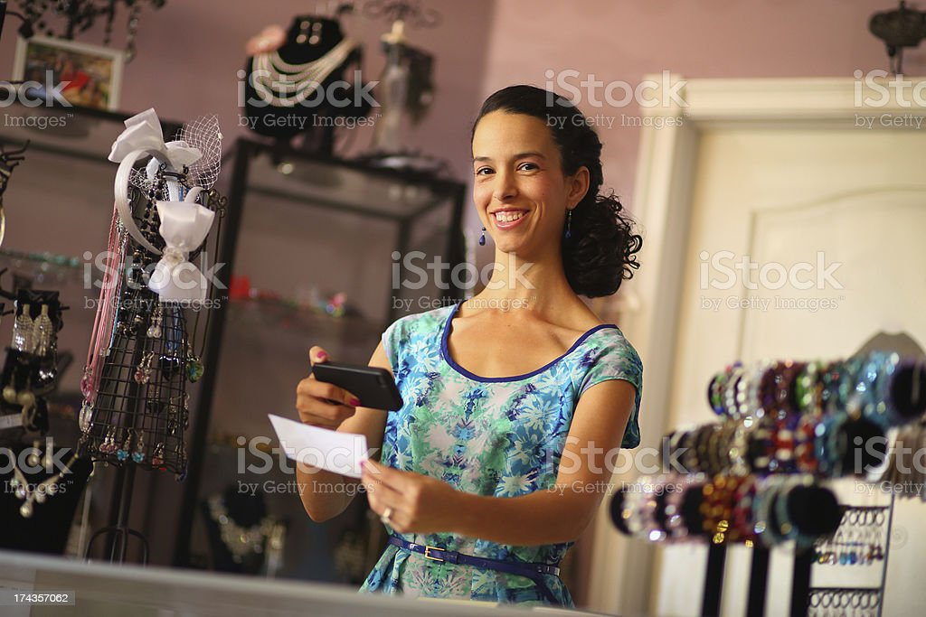 Hispanic Business Owner Depositing Check with Smart Phone stock photo