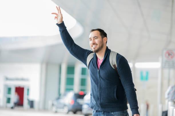 voyageurs d'affaires hispanique attraper taxi après vol à l'extérieur de l'aérogare - homme faire coucou voiture photos et images de collection