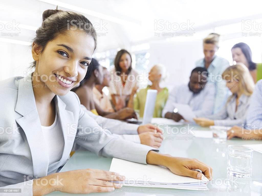 Hispanic business woman in conference with associates stock photo