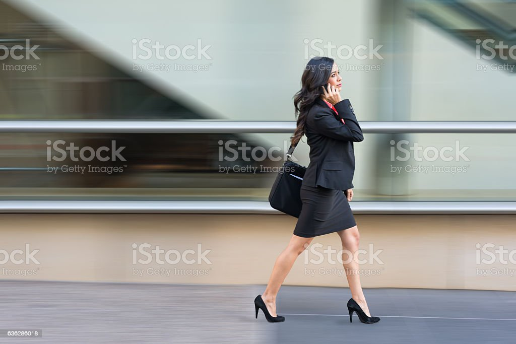 Hispanic Business Women On Phone Walking In A Rush stock photo