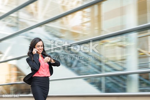 istock Hispanic Business Women On Phone Walking In A Rush 636897342