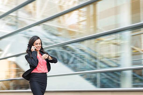 hispanic business women on phone walking in a rush - temps photos et images de collection