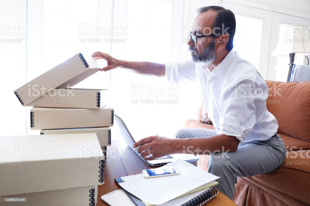 Hispanic Businessman Checking Inventory As He Works At Home Business stock photo